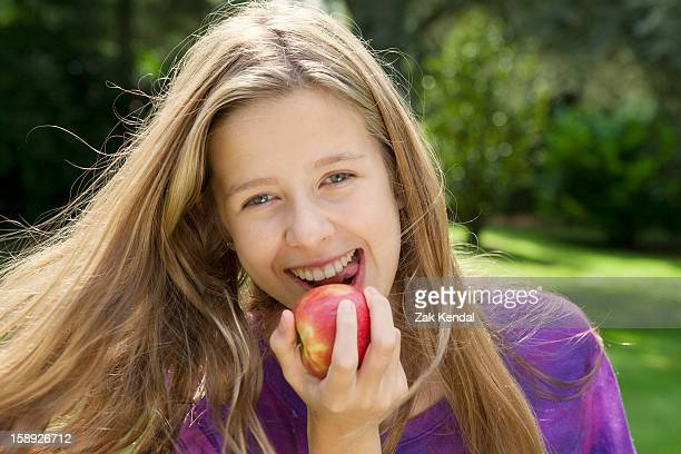 Smiling girl eating apple in park