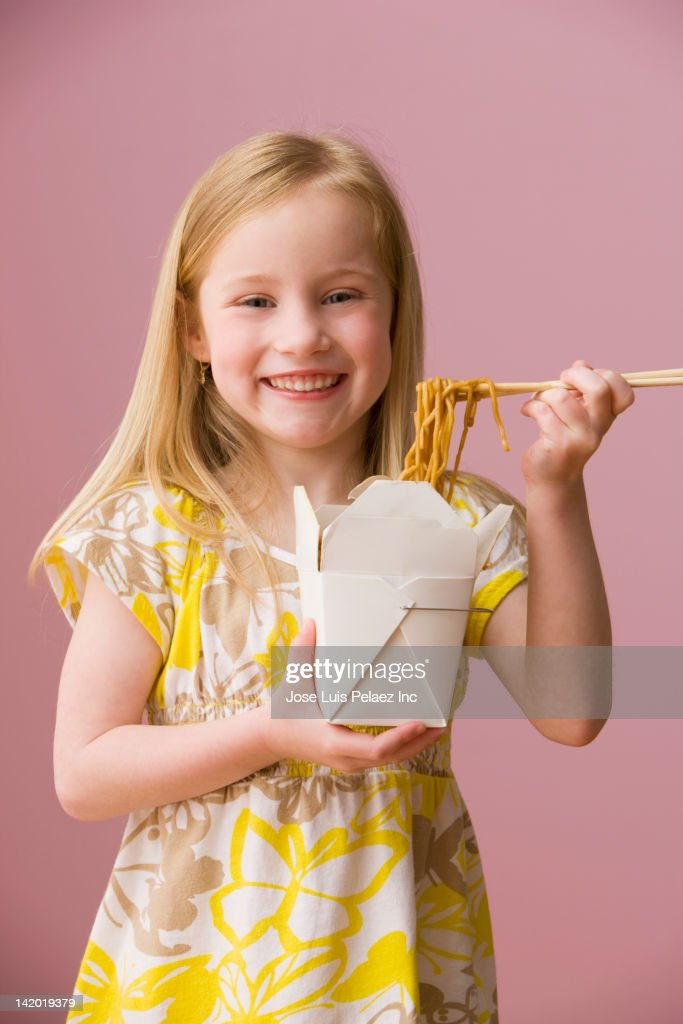 Smiling girl eating Asian food from carton : Stock Photo