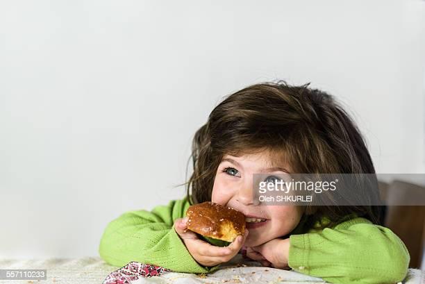 Smiling girl eating bread roll