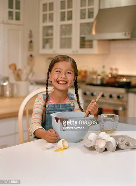 Smiling girl eating cake batter