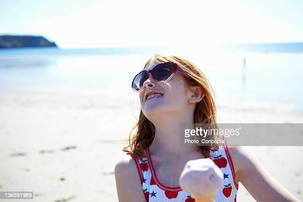Smiling girl eating ice cream on beach