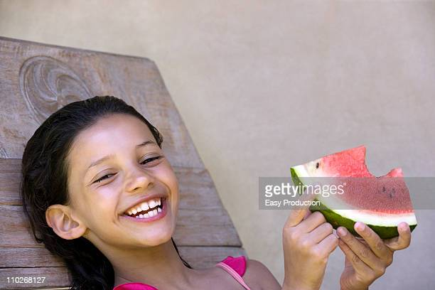 Smiling girl eating watermelon