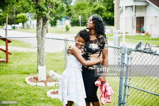Smiling girl embracing mother in front yard of home