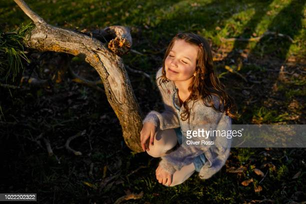 Smiling girl enjoying sunshine on a meadow at a tree
