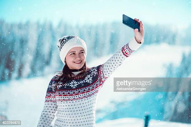 Smiling Girl Enjoying Winter and Taking Selfie while Snowing