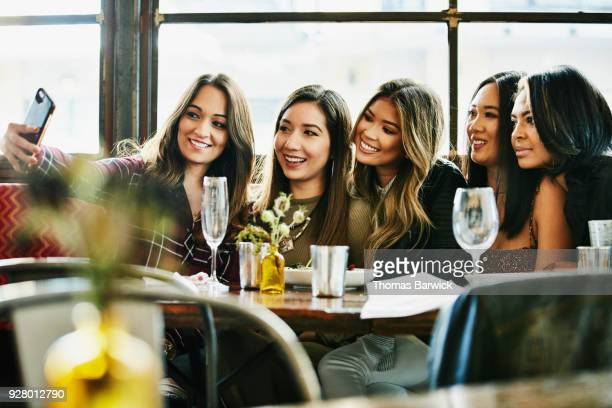 smiling girl friends taking selfie with smartphone during lunch party in restaurant - solo ragazze foto e immagini stock