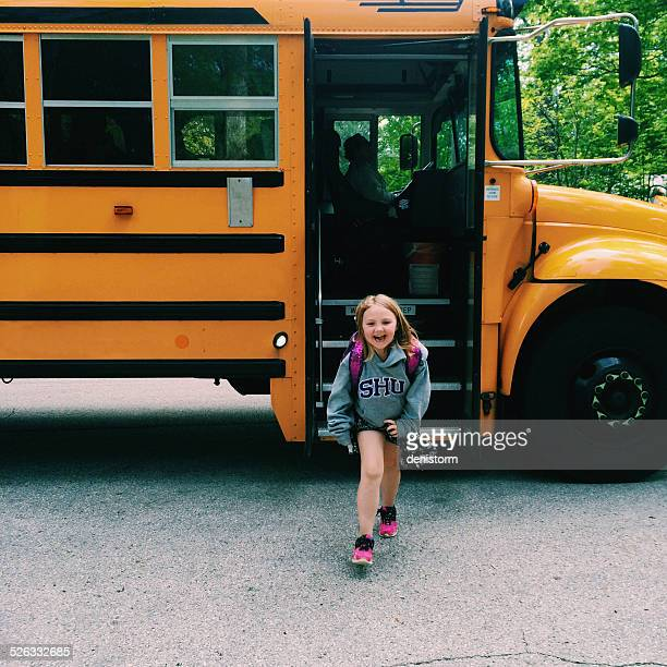 Smiling Girl getting off school bus, Wisconsin, America, USA