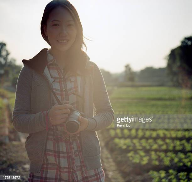 Smiling girl holding a camera on a lettuce field