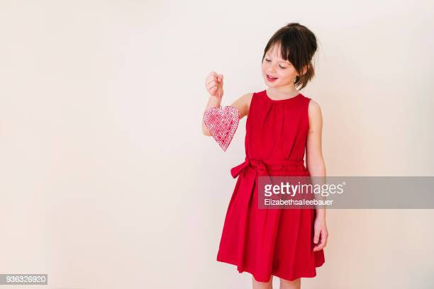 Smiling Girl holding a heart shape decoration