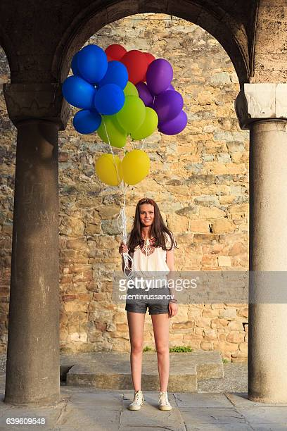 Smiling girl holding bunch of colorful balloons under columns