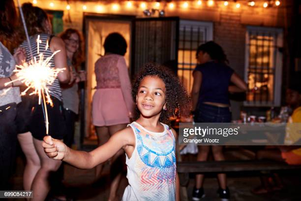 Smiling girl holding burning sparkler at backyard party