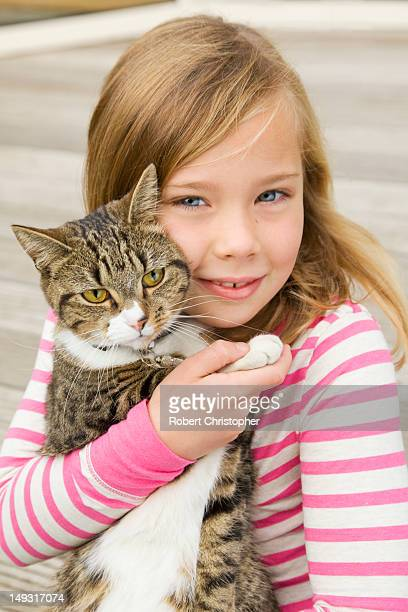 Smiling girl holding cat outdoors