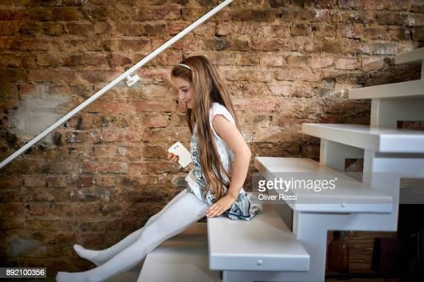 smiling girl holding cell phone sitting on stairs at home - children pantyhose stock photos and pictures