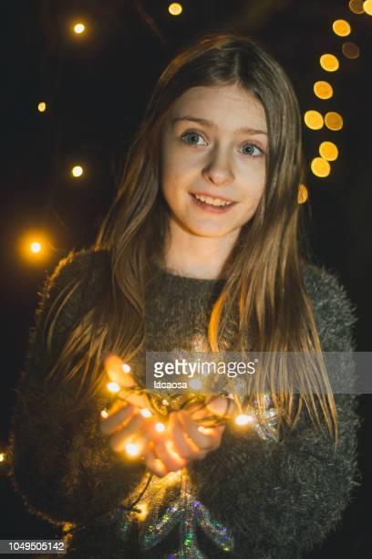 smiling girl holding christmas lights