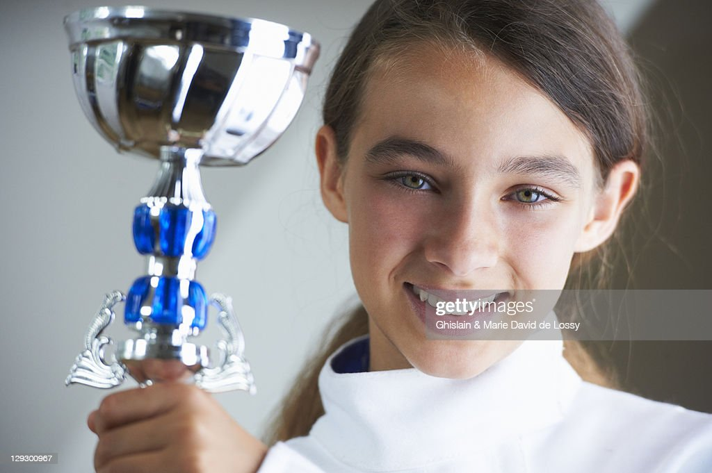 Smiling girl holding fencing trophy : Stock Photo