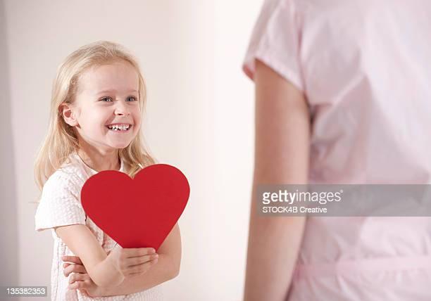 smiling girl holding heart in front of her mother - muttertag herz stock-fotos und bilder