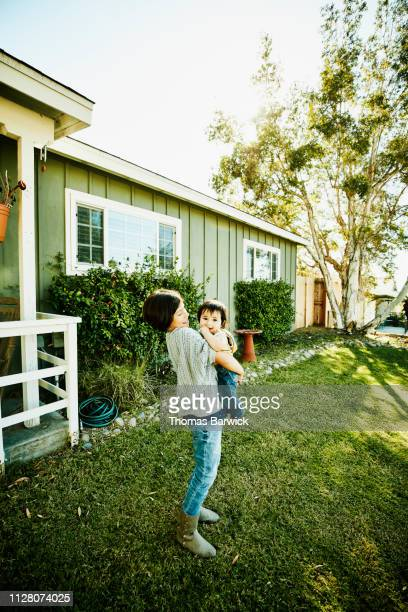 Smiling girl holding infant brother in front yard of home