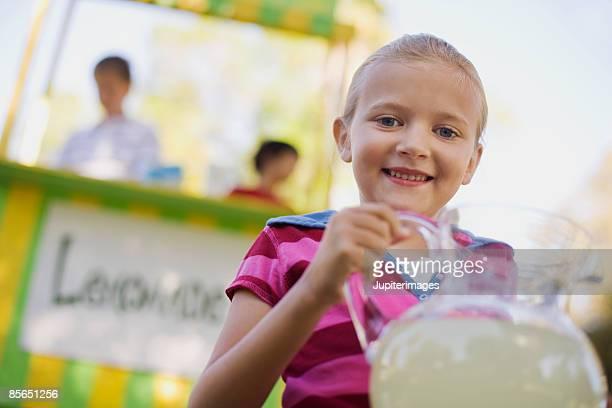 Smiling girl holding lemonade pitcher