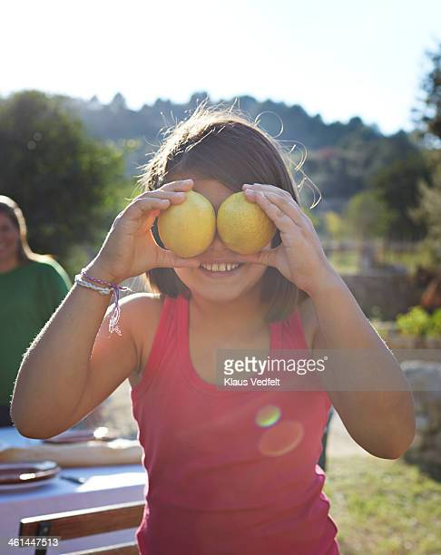 smiling girl holding lemons in front of eyes - klaus vedfelt mallorca stock pictures, royalty-free photos & images