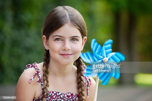 smiling girl holding pinwheel outdoors - paper windmill stock photos and pictures