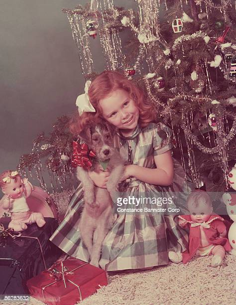 Smiling girl holding puppy by Christmas tree