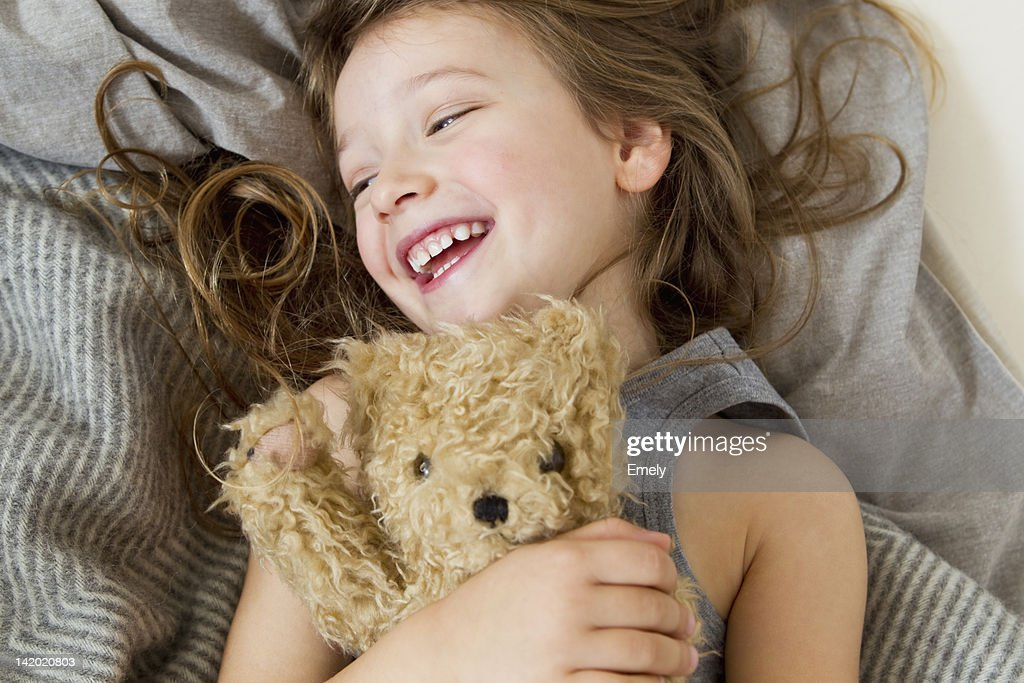 Smiling girl holding teddy bear in bed : Stock Photo