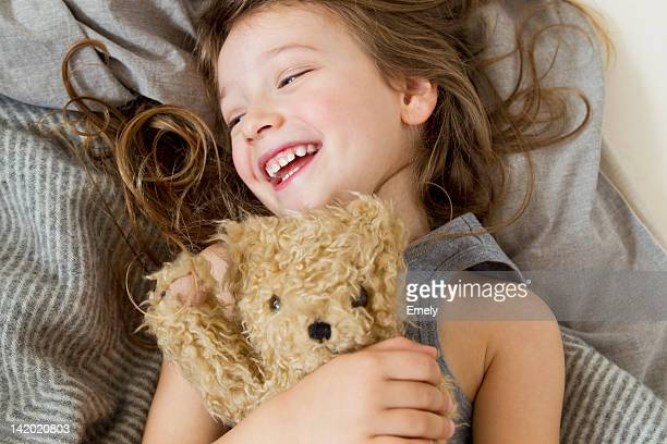 smiling girl holding teddy bear in bed - stuffed toy stock pictures, royalty-free photos & images