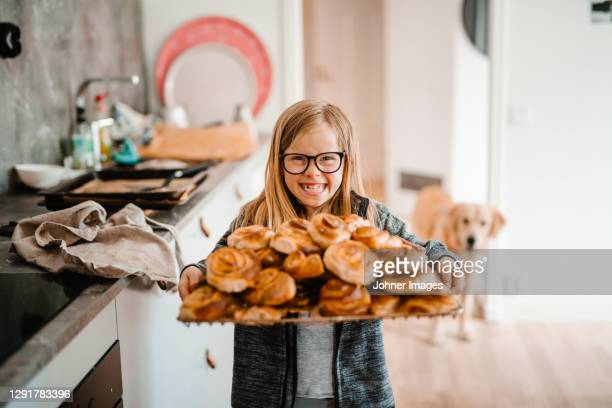 smiling girl holding tray with cinnamon buns - sweden stock pictures, royalty-free photos & images