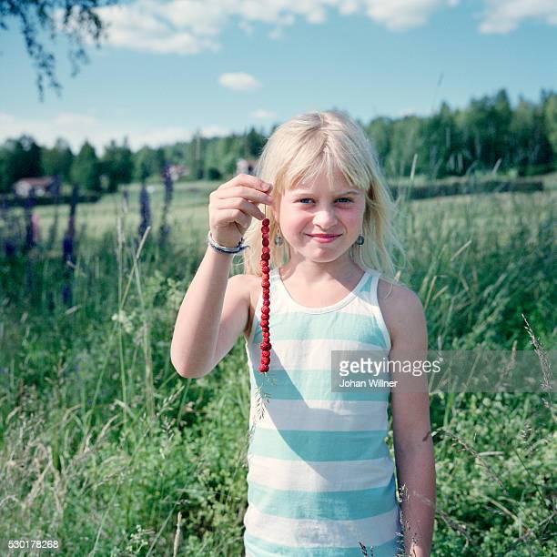 smiling girl holding wild strawberries - レクサンド ストックフォトと画像