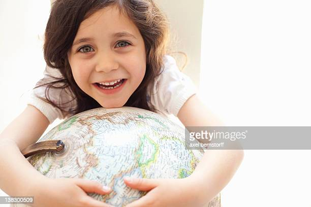 smiling girl hugging globe indoors - world kindness day fotografías e imágenes de stock