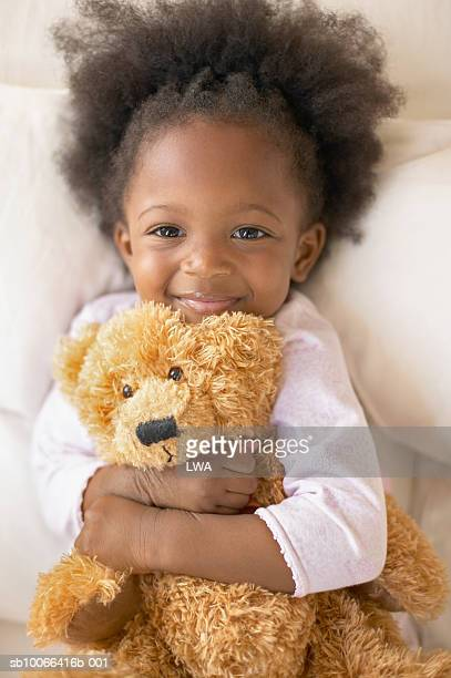 Smiling girl (2-3) hugging teddy bear, portrait