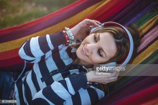 Leende flicka i en hängmatta som njuter av musik och liv