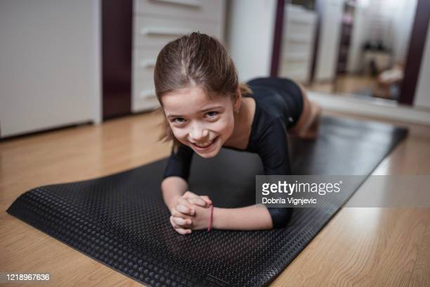 smiling girl in a plank position - physical education stock pictures, royalty-free photos & images
