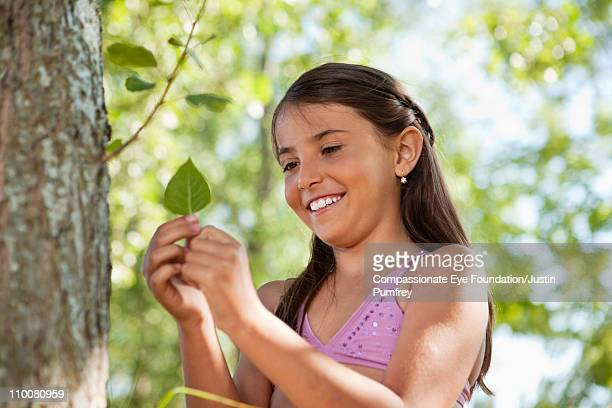 Smiling girl in bathing suit holding a leaf