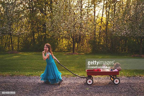 Smiling Girl in dress pulling wagon with doll and bear