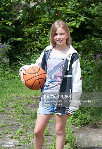 """smiling girl in garden holding basketball - """"compassionate eye"""" stock pictures, royalty-free photos & images"""