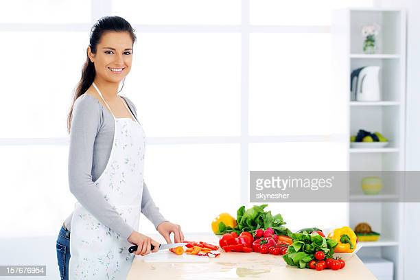 Smiling girl in her kitchen cutting vegetable ingredients.