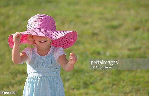 Smiling Girl in Oversized Pink Hat