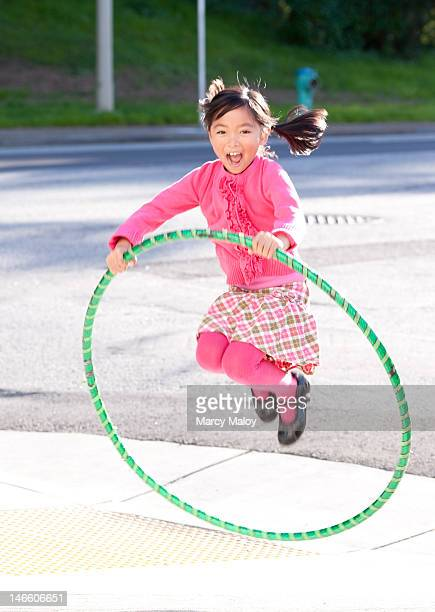 Smiling girl in pink jumping through a hula hoop.
