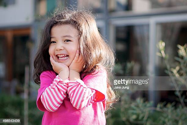 Smiling girl in pink shirt with hands on chin