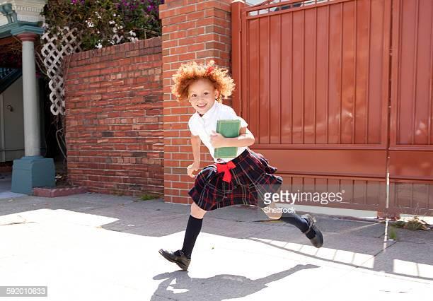 Smiling girl in school uniform running in driveway