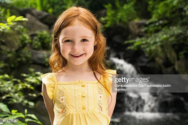 smiling girl in yellow dress by a waterfall - alleen kinderen stockfoto's en -beelden