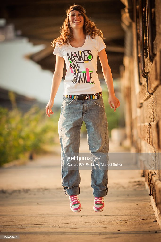 Smiling girl jumping for joy outdoors : Stock Photo