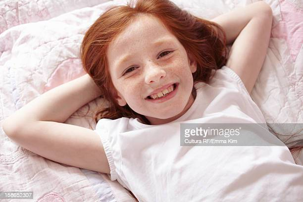 Smiling girl laying on bed