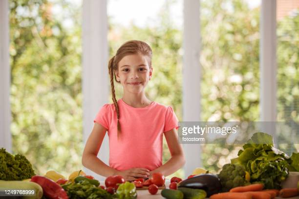 smiling girl leading a healthy life with abundance of fresh, colorful vegetables - zakelijke kleding stock pictures, royalty-free photos & images