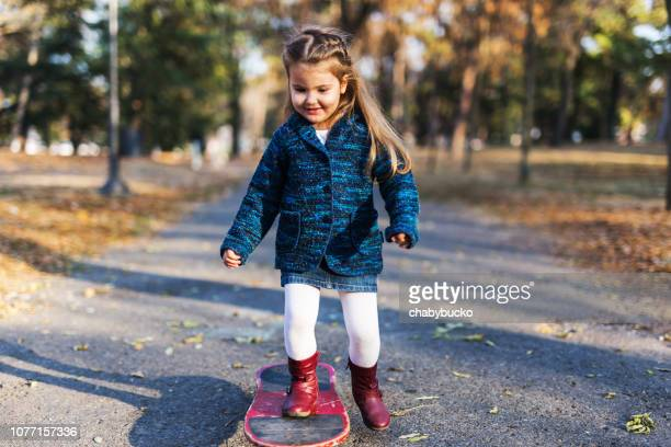 Smiling girl learning to drive skateboard