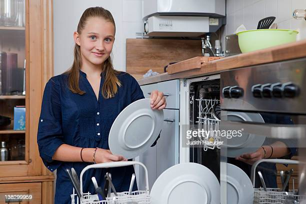 Smiling girl loading dishwasher