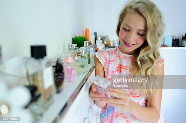 Smiling girl looking at perfume in bathroom