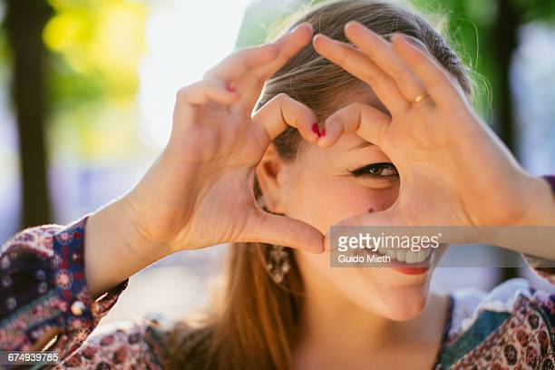 smiling girl looking through a heart. - gesturing stock pictures, royalty-free photos & images
