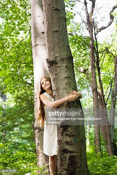 smiling girl looking up with arms around a tree